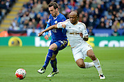 Leicester City defender Christian Fuchs and Swansea City striker Andre Ayew tussle for the ball during the Barclays Premier League match between Leicester City and Swansea City at the King Power Stadium, Leicester, England on 24 April 2016. Photo by Alan Franklin.