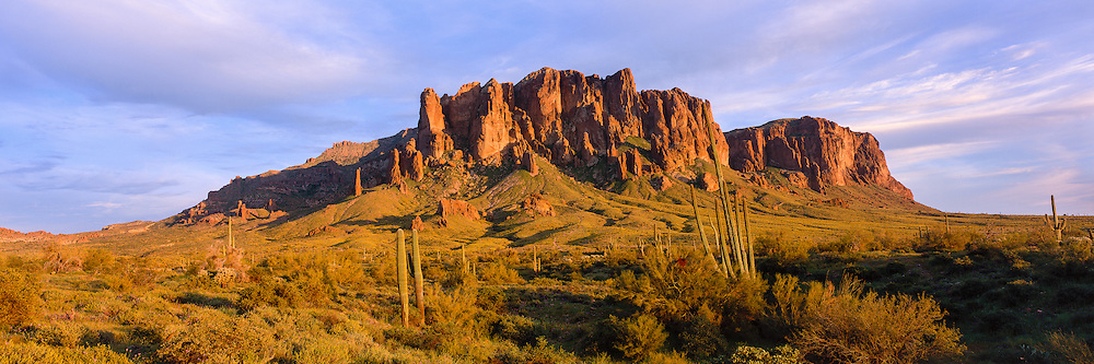 Setting sun lights the volcanic rock of the western face of the Superstition Mountains in the Sonoran Desert of Arizona