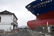A man cycles past a cargo ship, the 6175 dwt Asia Symphony, that has crashed into the sea wall after being swept inland by the March 11 tsunamis at the historic city of Kamaishi, Iwate Prefecture, Japan on 04 April, 2011. Photographer: Robert Gilhooly