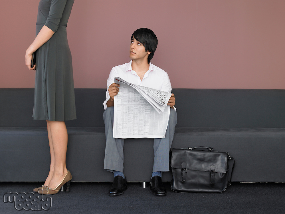 Businesswoman and Businessman Reading Newspaper in Lobby