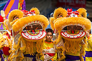 "05 JULY 2014 - BANGKOK, THAILAND: Chinese style lion dancers wait to perform on a side street in Bangkok during a parade for vassa. Vassa, called ""phansa"" in Thai, marks the beginning of the three months long Buddhist rains retreat when monks and novices stay in the temple for periods of intense meditation. Vassa officially starts July 11 but temples across Bangkok are holding events to mark the holiday all week.    PHOTO BY JACK KURTZ"