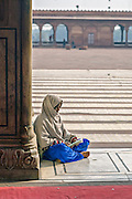 INDIA, OLD DELHI:  Young Muslim woman, barefoot with hijab, reading in the courtyard of the Jama Masjid Mosque in Old Delhi.