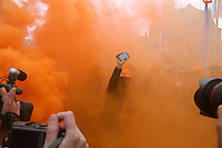 30th April 2013 Amsterdam, Netherlands. Dam Square. Queen Beatrix' abdication takes place, and her son Prince Willem-Alexander will be King of the Netherlands. Some Dutch make fun in orange clouds of smoke that came from some pots. Photographers gathered around the smoke