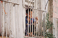 Boy looking outside his window in the Kurdish ghetto, Istanbul, Turkey.