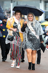 Ladies take cover from the rain during Boodles Ladies Day at Chester Racecourse.
