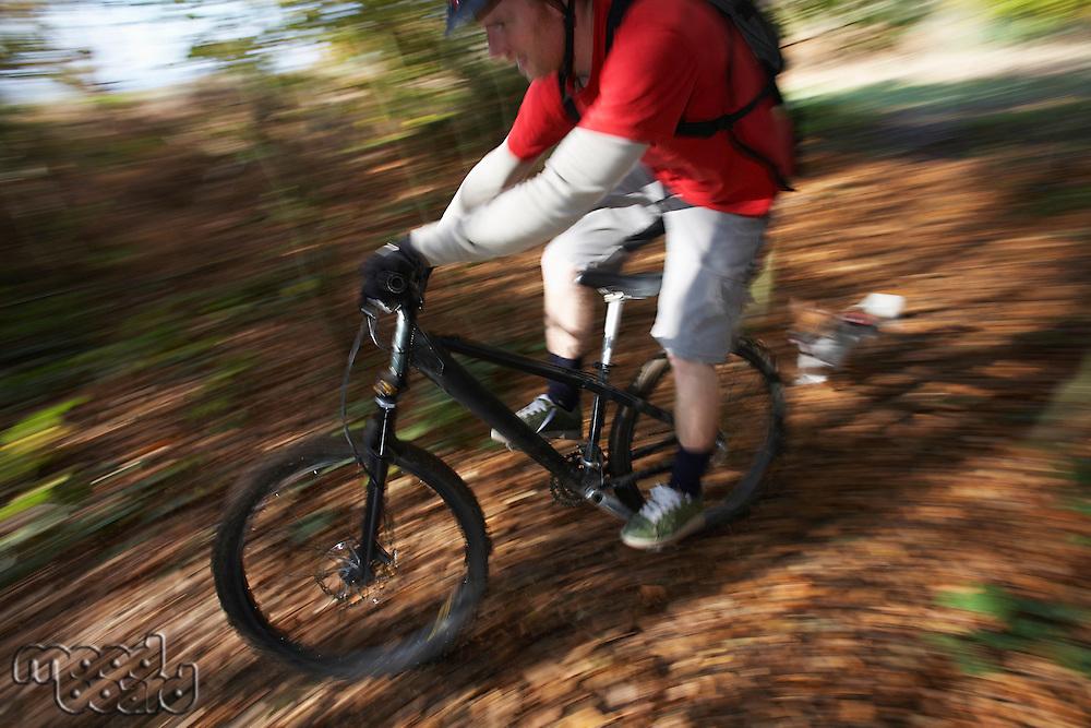 Dog chasing man on mountain bike through woodland motion blur