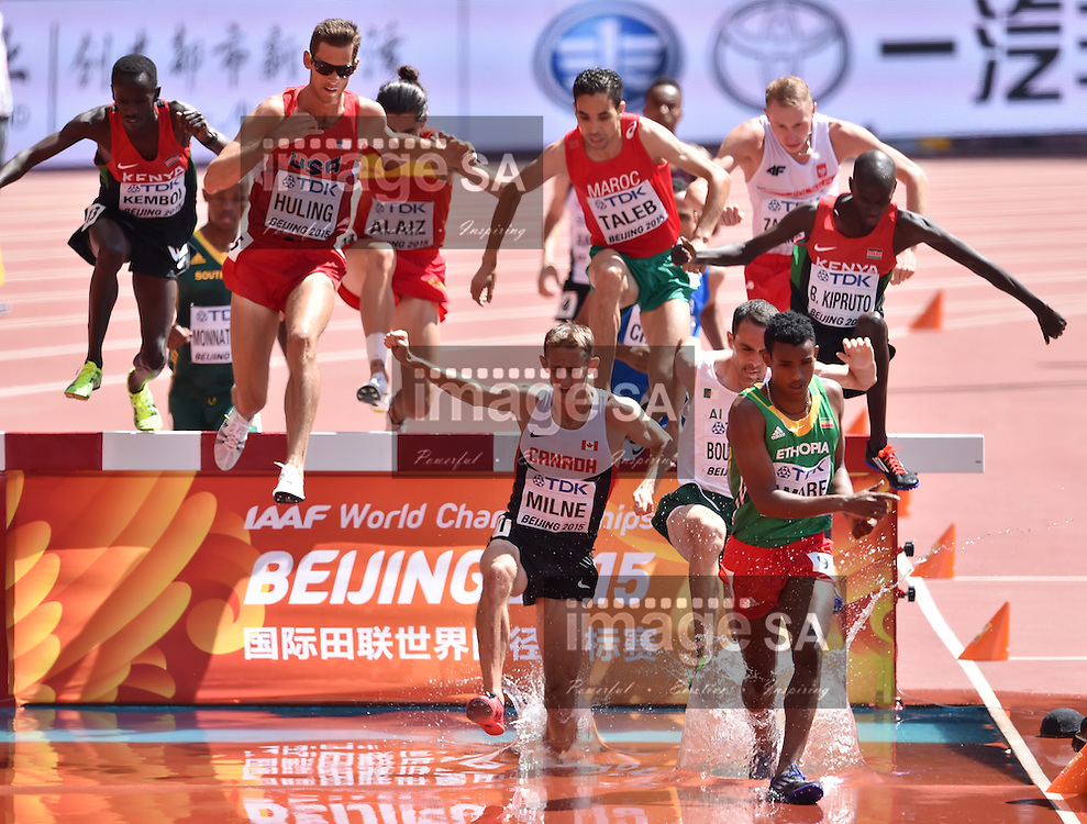 BEIJING, CHINA - AUGUST 22: Ezekiel Kemboi (Kenya), Daniel Huling (USA), Taylor Milne (Canada), Brahim Taleb (Morocco), Hicham Bouchicha (Algeria), Hailemariyam Amare (Ethiopia) and Brimin Kiprop Kipruto (Kenya) at the water jump in Round 1 of the mens 3000m steeplechase during day 1 of the 2015 IAAF World Championships at National Stadium on August 22, 2015 in Beijing, China. (Photo by Roger Sedres/Gallo Images)