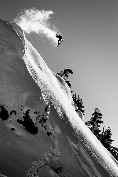 Black and White image of Pro snowboarder Dave Short doing a large frontside 360 in the Seagrams snowmobile zone, in the Whistler, BC backcountry on a beautiful clear winter day