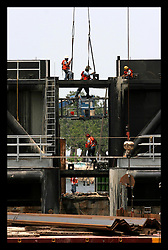 1 June, 2006. Lakeview, New Orleans, Louisiana. Contractors for the US Army Corps of Engineers work on the $50 million 17th Street Canal Interim Closure structure. The dam, designed to prevent water build up in the canal during hurricane storm surges is almost complete. Between 30 and 50 workers per 12 hour shift work around the clock, seven days a week to complete the dam. They continue to drive pilings into the water and have the center section left to complete. The barrier has yet to be automated with hydraulic lifts. For now the Army Corps must use cranes to manually close the structure. The pumping capacity is currently only 10% of pre hurricane Katrina levels, potentially leaving the affluent Lakeview neighbourhood unprotected.