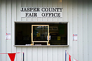 21 JULY 2020 - COLFAX, IOWA: A plexiglass shield in front of the window at the Jasper County Fair office in Colfax, about 30 miles east of Des Moines. Summer is county fair season in Iowa. Most of Iowa's 99 counties host their county fairs before the Iowa State Fair. In 2020, because of the COVID-19 (Coronavirus) pandemic, many county fairs were cancelled, or scaled back to concentrate on 4H livestock judging. The Iowa State Fair was cancelled completely. The Jasper County Fair cancelled most events and focused on just the 4H contests. Tuesday were the swine contests.                  PHOTO BY JACK KURTZ