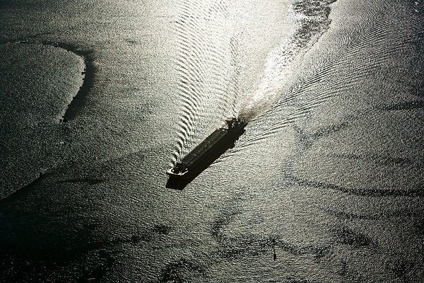 Aerial view of a barge passing through the Port of Houston at sunset