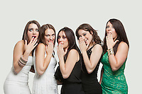 Portrait of five shocked young women with hands over mouth against gray background