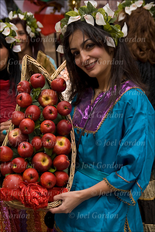 Portrait of smiling  Iranian American young woman, holding basket of apples, dressed in transitional folk costume from Kourdestan in northern Iran showing her ethnic pride, before the start of the 2011 Persian Iranian Parade in New York.