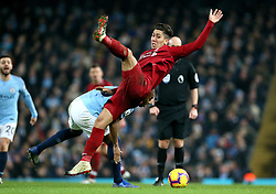 Liverpool's Roberto Firmino (right) and Manchester City's Fernandinho (left) battle for the ball during the Premier League match at the Etihad Stadium, Manchester.