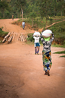 Women carry parchment to the drying tables for sorting at Cyarumba Washing Station, Maraba, southern Rwanda.