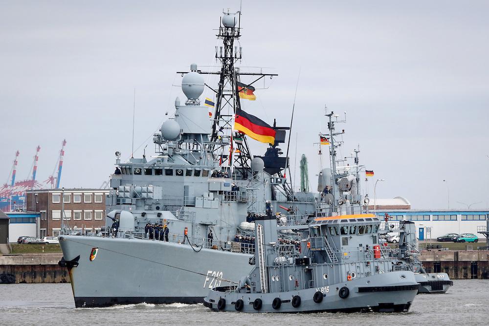 DEU, Deutschland, Wilhelmshaven, 24. Maerz 2016: Die  Fregatte F213 &quot;Augsburg&quot; der Bundesmarine wird im Marinehafen von Wilhelmshaven vom Schlepper &quot;Vogelsand&quot; an ihren Liegeplatz geschleppt. Das Schiff kehrt von einer mehrmonatigen Reise aus dem Persischen Golf zurueck, wo es den franzoesischen Flugzeugtraeger &quot;Charles de Gaulle&quot; bei der Operation &quot;Counter Daesh MAR&quot; im Kampf gegen den so genannten IS in Syrien und im Irak unterstuetzt hat. | DEU, Germany, Wilhelmshaven, March 24, 2016: A tug boat tows the frigate F213 &quot;Augsburg&quot; of the German Navy at the Navy port of Wilhelmshaven. The vessel returns from a mission in the Persian Gulf where it supported the French aircraft carrier &quot;Charles de Gaulle&quot; in the Operation &quot;Counter Daesh MAR&quot; against the so called IS in Syria and Iraq |<br /> <br /> [ CREDIT: www.fockestrangmann.de - MWSt./VAT/TVA  7 % - Focke Strangmann Fotos - Rossbachstr. 46 - 28201 B r e m e n - Germany - Tel.  +49.163.2513863  - ich@fockestrangmann.de - Bank: S p a r k a s s e B r e m e n  BLZ: 29150101 Konto: 10886646 IBAN: DE05 2905 0101 0010 8866 46 00 BIC: SBREDE22 Stnr. 602730314, FA Bremen, VAT DE225275020] <br /> <br /> [#0,26,121#]