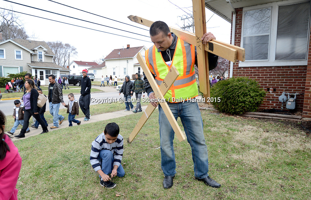 Laura Stoecker/lstoecker@dailyherald.com<br /> Carlos Gamino, 8, of Aurora stops to tie his shoe while he and his father, Raul, carry wooden crosses back to Sacred Heart Catholic Church after the Stations of the Cross walk in Aurora on Good Friday.