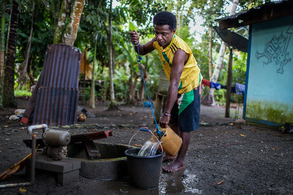 Yosua fills a bucket with water from the well so his sister could take a shower and get ready for school.