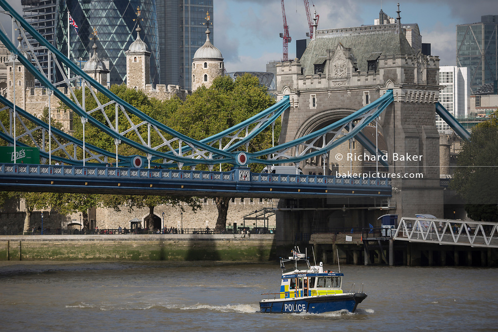 A met police launch boat in the waters of the River Thames beneath the Victorian-era Tower Bridge with the Norman Tower of London in the capital's financial district (aka The Square Mile) behind, on 5th October, 2017, in London, England. The Gabriel Franks is a Fast Response Targa 31 boat of the Metropolitan Police Marine Policing Unit, named after the first British marine police officer to be killed in the line of duty.