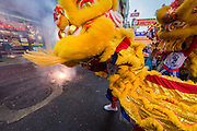 31 JANUARY 2014 - BANGKOK, THAILAND:   A Chinese Lion dancer performs in a  front of a jewelry shop on Yaowarat Road during Lunar New Year festivities, also know as Tet and Chinese New Year, in Bangkok. This year is the Year of the Horse. The Lion Dance scares away evil spirits and brings prosperity and luck. Ethnic Chinese make up about 14% of Thailand and Chinese holidays are widely celebrated in Thailand.     PHOTO BY JACK KURTZ