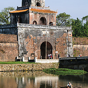 A man fishes in the moat in the shadow of a guard tower at the Imperial City in Hue, Vietnam. A self-enclosed and fortified palace, the complex includes the Purple Forbidden City, which was the inner sanctum of the imperial household, as well as temples, courtyards, gardens, and other buildings. Much of the Imperial City was damaged or destroyed during the Vietnam War. It is now designated as a UNESCO World Heritage site.