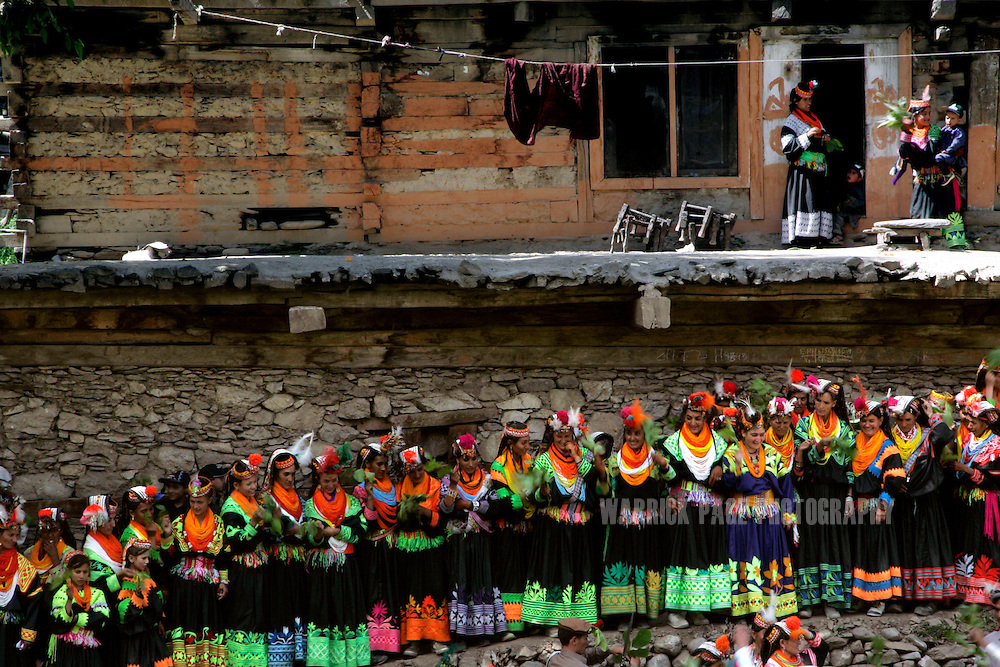 "KALASHA VALLEYS, PAKISTAN - MAY 16: Kalash women gather to wave walnut-branches in unison, which is believed to attract fairies and bless the new life during the ""Joshi"" (spring) festival in the village of Batrik May 16, 2008 in the Kalasha Valleys, northwestern Pakistan. The Joshi Festival is a celebration of dance, music and prayer to welcome the coming of warmer season and the new life and crops it brings. The shrinking Kalash community of 4000, who claim to be descendants of Alexander the Great and worship several gods, are considered by many Pakistanis to be unclean, lazy and heretics. They often face ridicule and persecution for their polytheistic religion and fear the spread of hard-line Islamism bordering their communities.  (Photo by Warrick Page)"