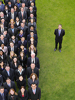 Business man standing next to large group of business people in formation elevated view portrait