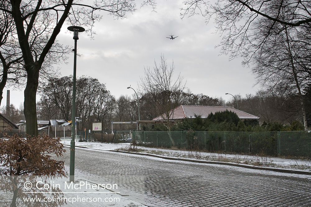 An aircraft flying over Am Bürgerpark, a road on the site of the former Berlin Wall, in Pankow, a district of northern Berlin. The route of the Wall, which stood from 1962-1989, has been developed into the 'Mauerweg,' a thoroughfare which traces most of the route of the Wall which encircled the city and divided it into East and West Berlin during the Cold War. In the years following the 1989 civil uprising in the German Democratic Republic, most of the Wall was removed as part of the reunification strategy which united the pro-Soviet DDR and the Federal Republic of (West) Germany.