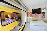 LUOYANG, CHINA - DECEMBER 16: (CHINA OUT) <br /> <br /> Space Capsule Hotel <br /> <br /> A woman watches TV at a hotel built as a space capsule on December 16, 2014 in Luoyang, Henan province of China. A hotel built its inner rooms as space capsules where televisions, kitchens, wash rooms and other necessary facilities were fully equipped. They were divided into economy classes and deluxe classes with its cheapest charge for 45 RMB to 55 RMB (about 7.2 to 8.8 USD) per night.<br /> ©Exclusivepix Media