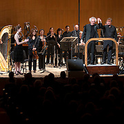 """June 8, 2012 - New York, NY : Conductor David Robertson, standing on platform at right, takes the hand of composer Michael Jarrell, standing on platform at left, after the New York Philharmonic performed the U.S. premiere of Mr. Jarrell's 'NACHLESE Vb: Liederzyklus' (2011) during The Metropolitan Museum of Art's Presentation of """"CONTACT!,"""" the new-music series of the New York Philharmonic, on Friday night. CREDIT: Karsten Moran for The New York Times"""