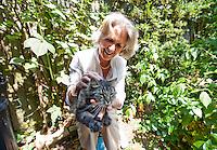 Senior woman cuddling cat while sitting in garden