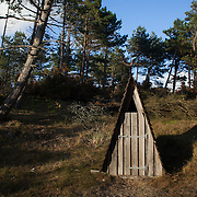 A wooden compost toilet near Lodbjerg Light House. The light house is in a national park of heathland and forrest near the West coast of Denmark. Next to the light house is a camp site with no other facilities than a fire place, a shelter and a compost toilet. The national park is popular amongst hikers.