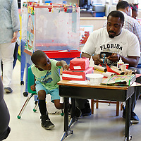 "Thomas Wells | Buy at PHOTOS.DJOURNAL.COM<br /> Trenton Brewer, 4, can't seem to wait for his father, Theodus, to finish building their fire truck before starting to play with it at Thursday's ""Building with Dad"" program."