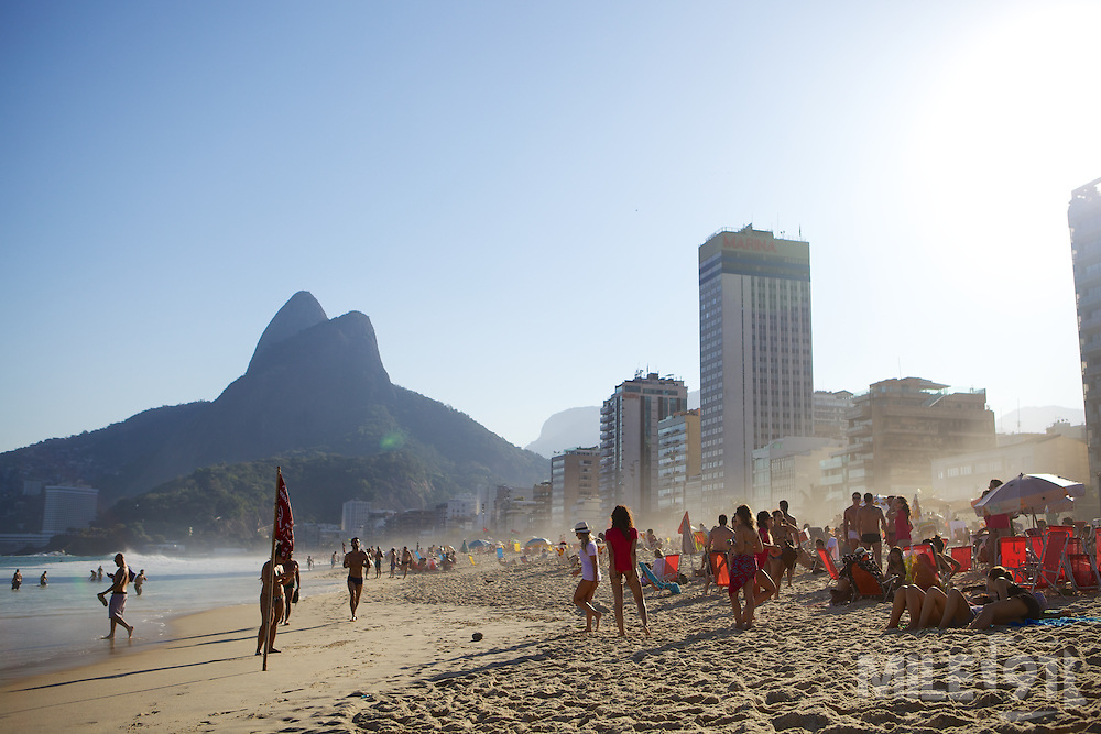 A beach scene with mountains, skyscrapers and the sea, Rio de Janeiro, Brazil.
