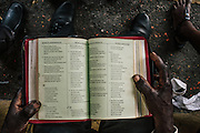 Jose Manuel Gustavo reads a bible in creole while he waits outside the Interior Ministry in Santo Domingo. He waited in line for three days.