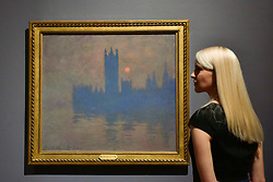 "© Licensed to London News Pictures. 30/10/2017. London, UK.  A staff member views ""Houses of Parliament, Sunset"", 1904, by Claude Monet at a preview of ""Impressionists in London, French Artists in Exile (1870-1904)"" at Tate Britain.  The exhibition brings together over 100 works by Monet, Tissot, Pissarro and others in the first scale show of French artists who sought refuge in Britain during the Franco-Prussian War and shows views of London as seen through French eyes.  The exhibition runs 2 November 2017 to 29 April 2018.  Photo credit: Stephen Chung/LNP"