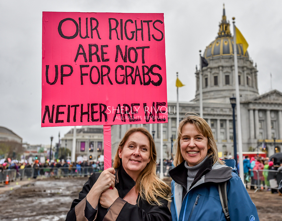 "Two women stand at Civic Center Plaza holding a sign reading, ""Our rights are not up for grabs. Neither are we."""
