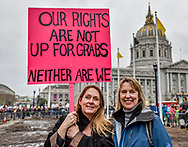 """Two women stand at Civic Center Plaza holding a sign reading, """"Our rights are not up for grabs. Neither are we."""""""