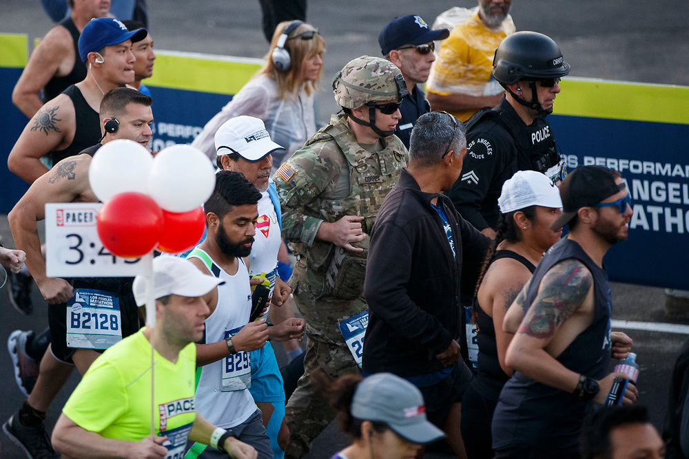 "A soldier, LAPD Senior lead Officer Joe Cirrito, right, and other law enforcement officers run in full tactical gear to honor slain Whittier Police Department Officer Keith Boyer wear full tactical gear while running at the start of the 32nd annual Los Angeles Marathon at Dodger Stadium on Sunday morning, March 19, 2017 in Los Angeles, Calif.  The 26.2-mile ""Stadium to the Sea"" route begins at Dodger Stadium and ends at Ocean and California avenues in Santa Monica. © 2017 Patrick T. Fallon"