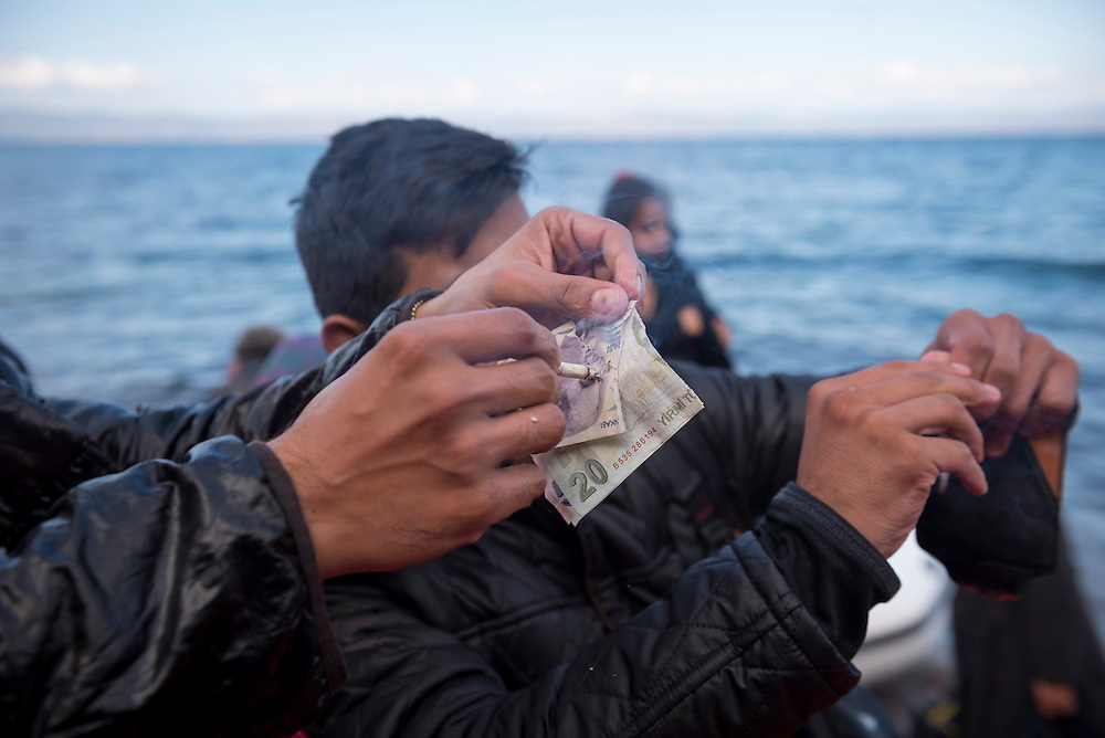Minutes after an inflatable boat crowded with migrants landed on the north coast of the Greek island of Lesbos from Turkey, two of the migrants tear up and deface the Turkish currency that remained in their pockets. Many migrants tell of abuse and other bad experiences in Turkey.