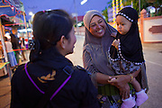 29 SEPTEMBER 2009 -- YARANG, PATTANI, THAILAND: A Thai woman Ranger talks to a Muslim woman and her daughter during a security operation at a street fair in Yarang, Pattani, Thailand. The 39 women in the 44th Army Ranger Regiment are the only Thai women seeing front line active duty against Moslem insurgents in Thailand's deep south provinces of Pattani, Narathiwat and Yala. All of the other women serving in Thai security services are employed as office and clerical workers. The Ranger women are based at the Ranger camp in the Buddhist village of Baan Trokbon in Sai Buri district of Pattani province. The unit was formed in 2006 after Muslims complained about the way Thai soldiers, all men, treated Muslim women at roadblocks and during security sweeps. The women are frequently called upon to back up Thai regular army units when they are expected to encounter a large number of Muslim women. At least two of the women have been killed by Muslim insurgents. The unit has both Muslim and Buddhist members. Many of the women in the unit joined after either their fathers or husbands were killed by insurgents.   PHOTO BY JACK KURTZ