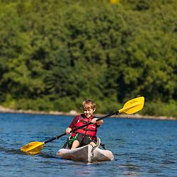 A boy paddles a kayak on Deboullie Pond in Aroostook County, Maine. Deboullie Public Reserve Land.
