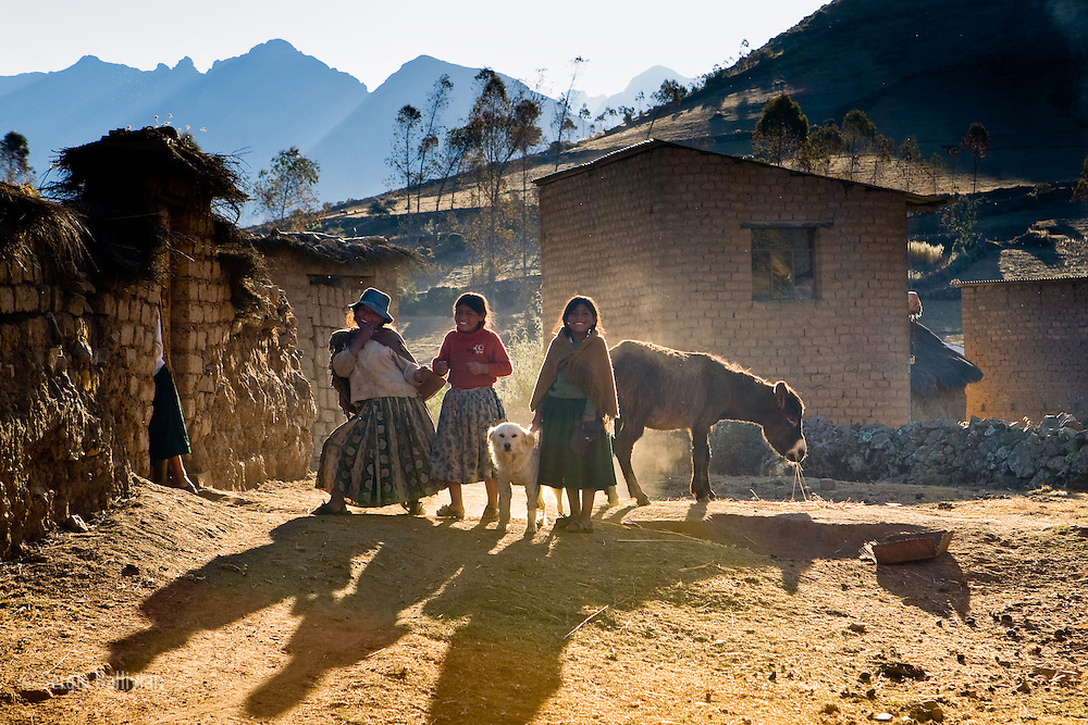 Young Quechua girls enjoy a moment of playfullness before the sun sets in the Apolobamba Range of the Andes in western Bolivia.  For the farmers in this region working the land is a day-long endeavor to eek out a living from steep, rocky and rugged mountains.