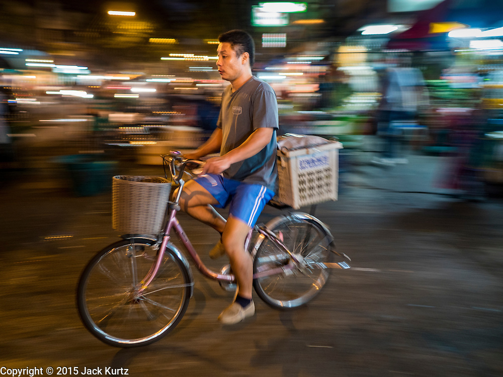 "21 DECEMBER 2015 - BANGKOK, THAILAND:  A man rides his bike past Pak Khlong Talat, also called the Flower Market. The market has been a Bangkok landmark for more than 50 years and is the largest wholesale flower market in Bangkok. A recent renovation resulted in many stalls being closed to make room for chain restaurants to attract tourists. Now Bangkok city officials are threatening to evict sidewalk vendors who line the outside of the market. Evicting the sidewalk vendors is a part of a citywide effort to ""clean up"" Bangkok.      PHOTO BY JACK KURTZ"