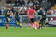 red card as Crawley Town defender Mark Connolly is fouled by Lincoln City midfielder Lee Frecklington during the EFL Sky Bet League 2 match between Lincoln City and Crawley Town at Sincil Bank, Lincoln, United Kingdom on 8 September 2018.