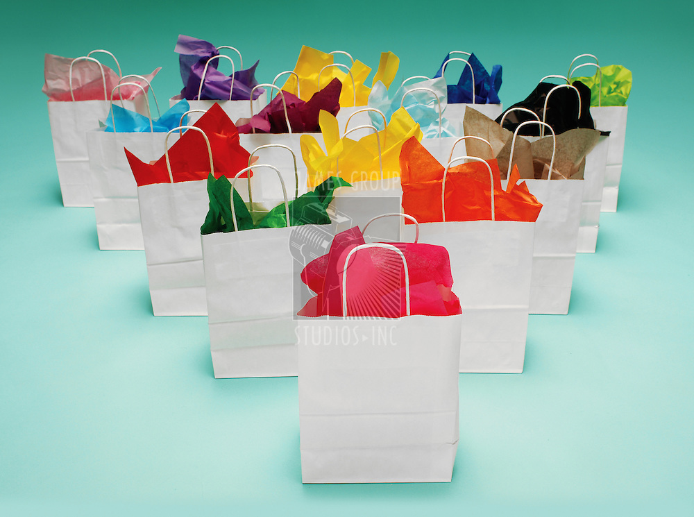 White shopping bags with colorful tissue paper on a teal green background