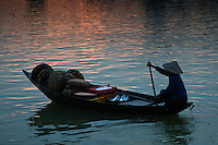 Woman wearing a conical hat rowing along the Thu Bon river in Hoi An at sunrise.
