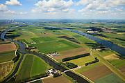 Nederland, Brabant, Gemeente Waspik, 12-06-2009; Overdiepsche polder, in de lengterichting van de Bergsche Maas (rechts) gezien naar Raamsdonksveer. In het kader van 'Ruimte voor de Rivier' (bescherming tegen hoogwater door rivierverruiming), zijn er plannen om de Overdiepse Polder te gebruiken om extra rivierwater af te voeren. De bestaande boerderijen moeten op terpen komen, de dijk langs de Bergse Maas wordt verlaagd terwijl bij het Oude Maasje een nieuwe dijk komt als primaire waterkering..Depoldering of Overdiep Polder.luchtfoto (toeslag), aerial photo (additional fee required).foto/photo Siebe Swart