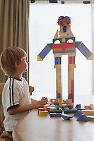 Boy (5-6) playing with building blocks at table