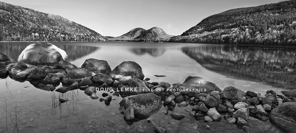 Mountains called The Bubbles in the background and boulders In the foreground at Jordan Pond on a beautiful autumn morning In Acadia National Park, Maine, USA